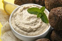Delicious chick-pea hummus with falafel balls and pita bread.  Garnished with mint and lemon.