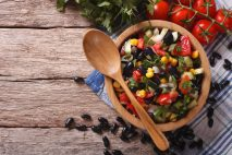 Mexican vegetable salad with black beans in a wooden bowl, close-up and ingredients on the table. Horizontal top view