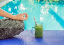 Closeup of a woman's hands during meditation with a green smoothies of spinach, orange and banana on the background of the pool.